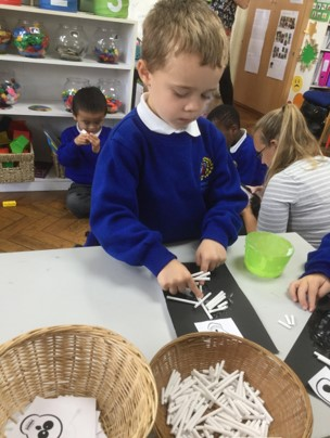 A young Dartford Primary Academy student is shown participating in an Arts and Crafts class.