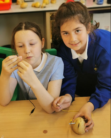 Two young girls in blue uniform holding a potato circuit